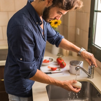 Side view of man washing white radish in the sink