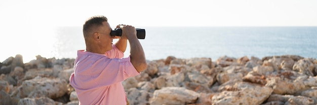 Side view man watching through binoculars