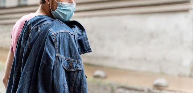 コピースペースと屋外で医療マスクを身に着けている側面図の男