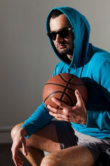 Side view of man wearing a hoodie posing while holding basketball