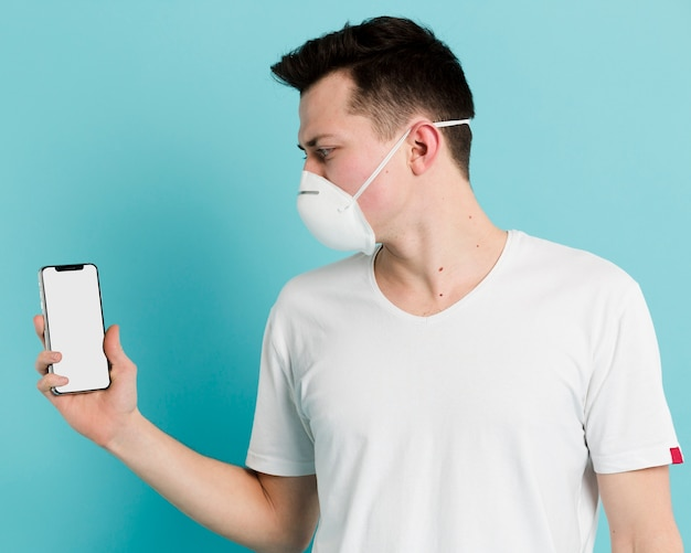 Side view of man wearing medical mask and holding up his smartphone