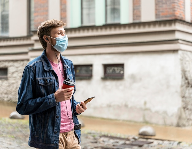 Side view man wearing a medical mask outside with copy space