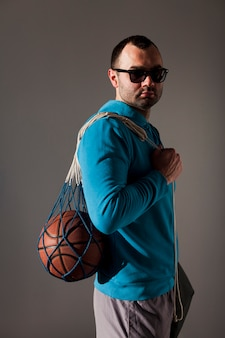 Side view of man wearing sunglasses holding basketball in net over shoulder