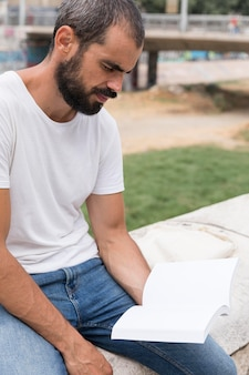 Side view of man with beard outside reading book