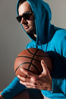 Side view of man with hoodie and sunglasses posing while holding basketball