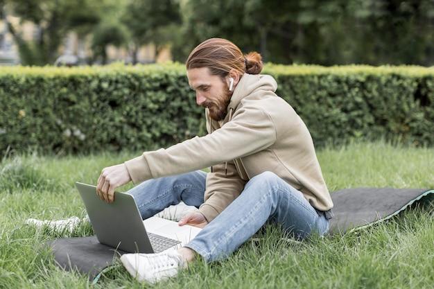 Vista laterale dell'uomo con il computer portatile in parco