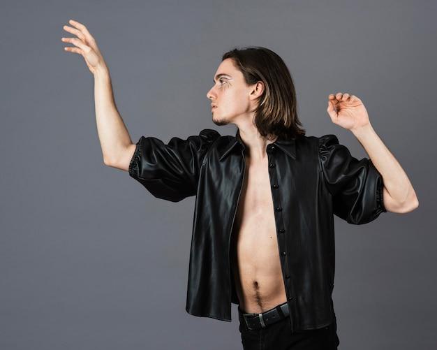 Vista laterale dell'uomo con trucco e giacca di pelle