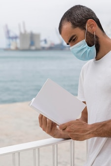 Side view of man with medical mask by the lake reading book