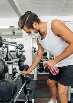 Side view of man with medical mask disinfecting gym equipment