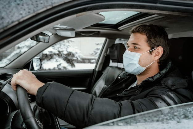 Side view of man with medical mask driving car for a road trip