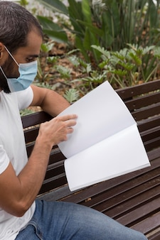 Side view of man with medical mask reading book on bench outdoors