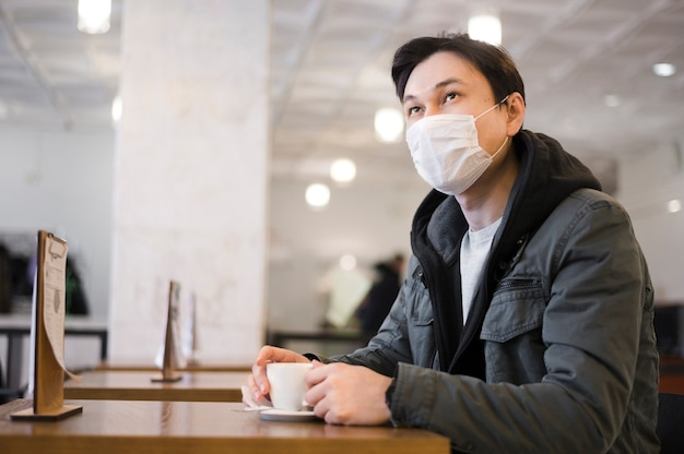 Side view of man with medical mask sitting at a table to have coffee