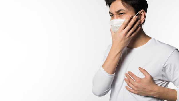 Side view of man with medical mask touching his chest