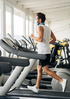 Side view of man with medical mask on the treadmill at the gym