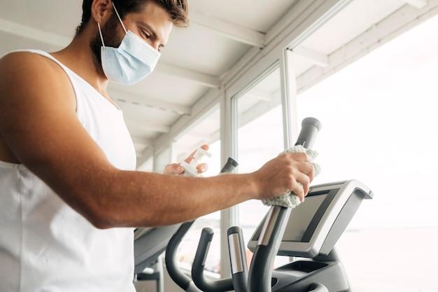 Vista laterale dell'uomo con mascherina medica utilizzando attrezzature da palestra