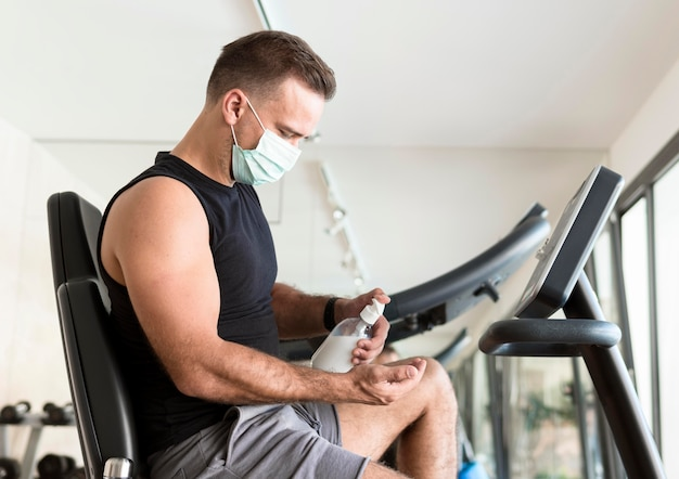 Side view of man with medical mask using hand sanitizer at the gym