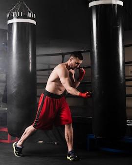 Вид сбоку человек с красными перчатками бокс