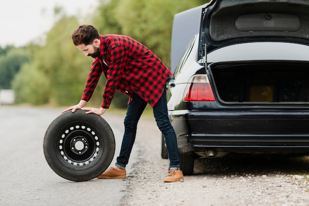Side view of man with spare tyre