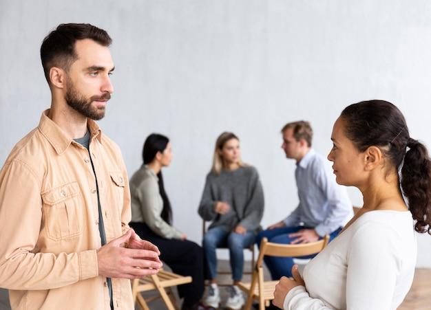 Vista laterale di un uomo e di una donna che conversano in una sessione di terapia di gruppo