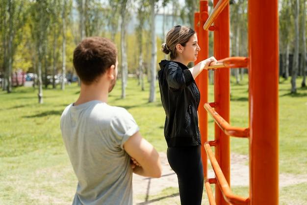 Vista laterale di un uomo e di una donna che esercitano insieme all'aperto