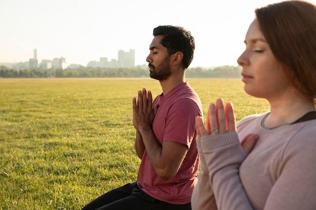 Vista laterale dell'uomo e della donna che meditano all'aperto con lo spazio della copia