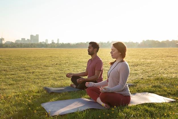 Vista laterale dell'uomo e della donna che meditano all'aperto su stuoie di yoga