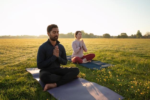 Vista laterale dell'uomo e della donna che meditano all'aperto