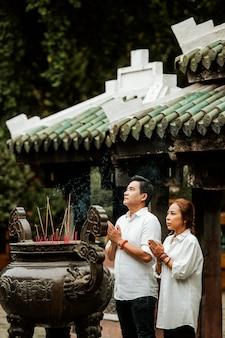 Vista laterale di un uomo e di una donna che prega al tempio con incenso ardente