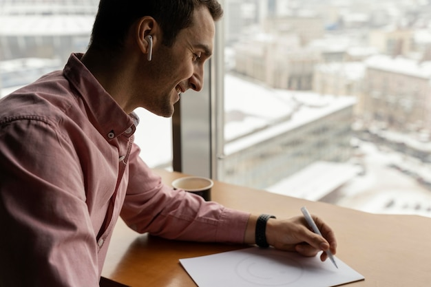 Side view of man at work with earphones and documents