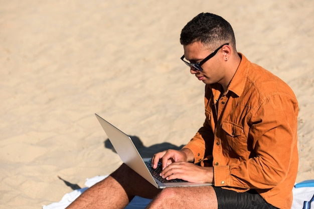 Side view of man working on laptop at the beach