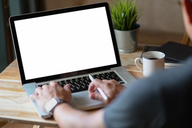 노트북을 사용하는 측면보기 남자는 코너 사무실에서 작업 테이블에 있습니다