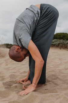 Side view of man in yoga position outdoors