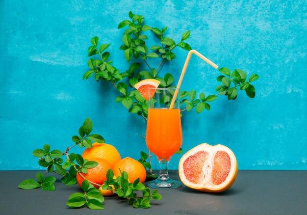 Вид сбоку мандаринов с листьями, апельсином и соком на голубой текстурированной поверхности. горизонтальный