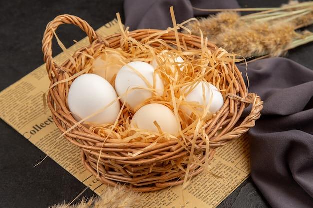 Vista laterale di molte uova organiche in un cesto su un vecchio giornale su un asciugamano nero su sfondo scuro