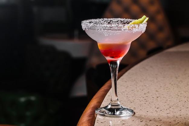 Vista laterale cocktail margarita con fetta di lime nel bicchiere