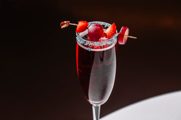 Side view martini cocktail with strawberry and grape in champagne glass