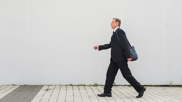 Side view of a mature businessman walking on pavement