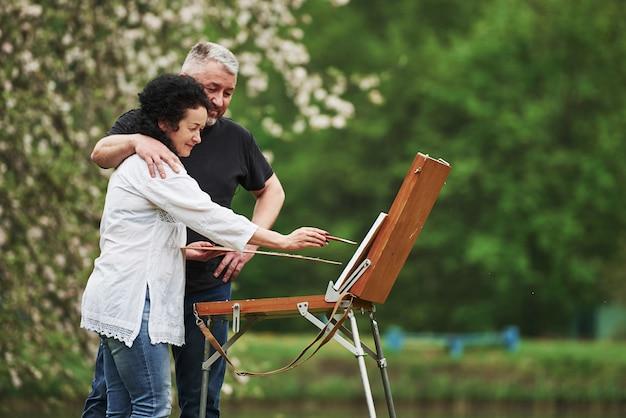 Вид сбоку. пожилая пара отдыхает и вместе работает над краской в парке