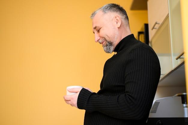 Вид сбоку зрелый мужчина держит чашку кофе