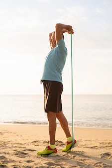 Side view of mature man working out with elastic rope on the beach