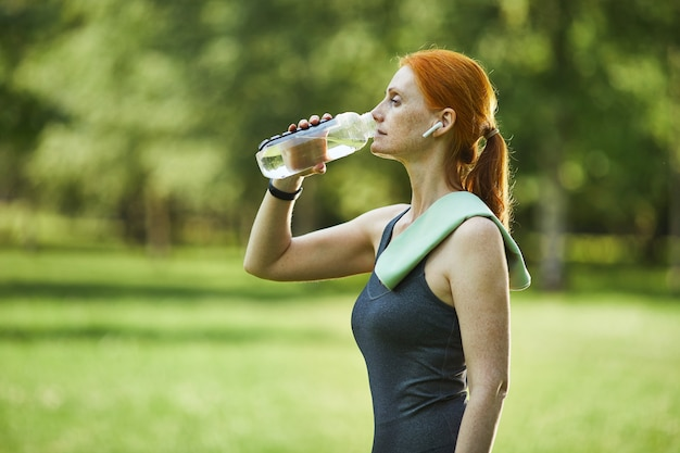 Side view of mature redhead fitness woman with towel on shoulder drinking water in park after exercising