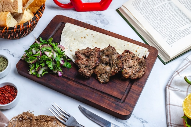 Side view meat basturma kebab on pita bread with herbs and onions on a board