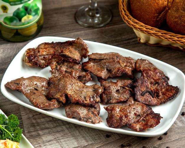 Kebab del basturma della carne di vista laterale su un piatto con pane