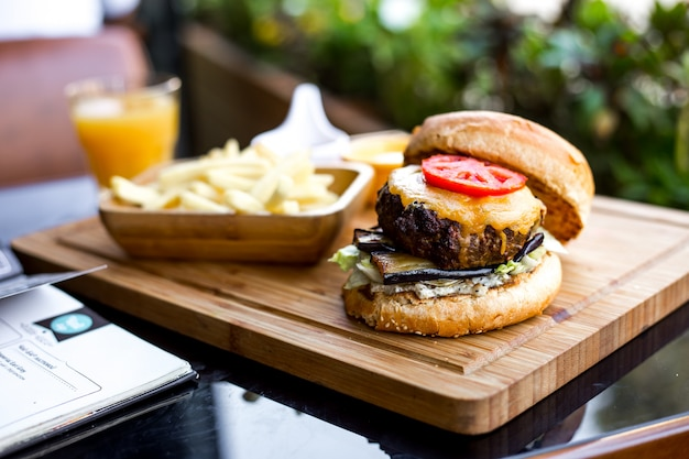 Hamburger di carne vista laterale con patatine fritte