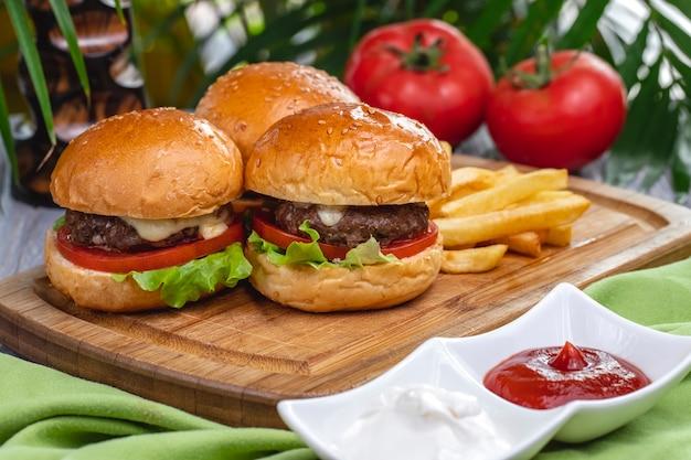 Вид сбоку мясные котлеты с картофелем фри, кетчупом и майонезом на доске