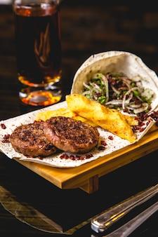 Вид сбоку мясные котлеты на гриле с луком, картофельным луком и гранатом на лаваш с бокалом пива на столе