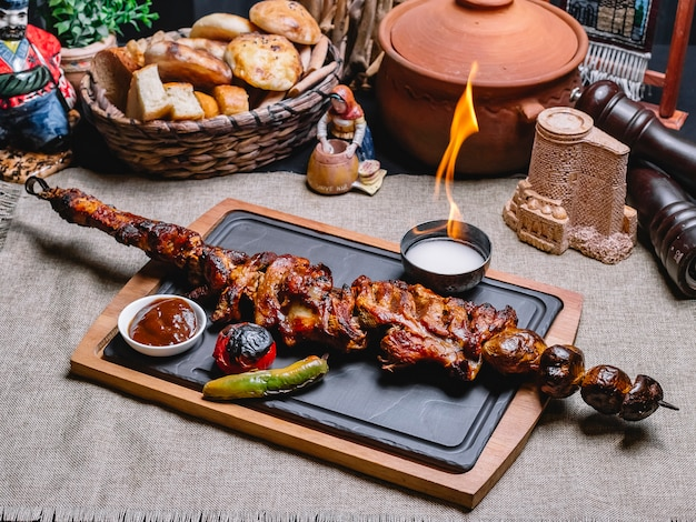 Side view meat kebab on a skewer with grilled potatoes and vegetables with sauce and fire on a board