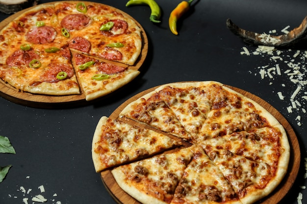 Side view meat pizza on a tray with salami pizza and hot peppers on black table