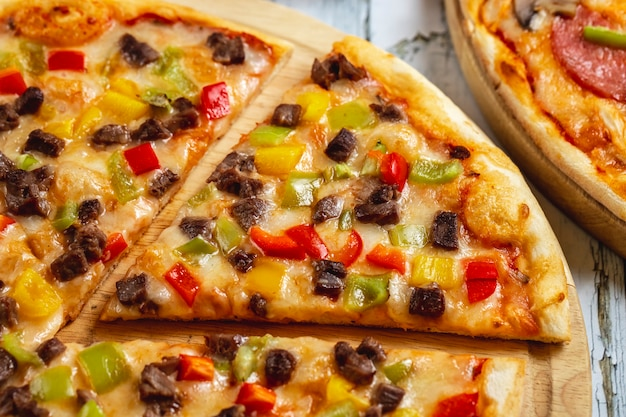 赤黄色と緑のピーマンの肉とチーズのサイドビュー肉ピザ
