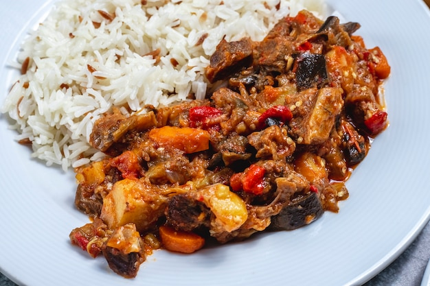 Side view meat stew lamb stew with fried onion and dried fruits with rice on a plate